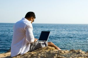 Advisor with laptop at beach